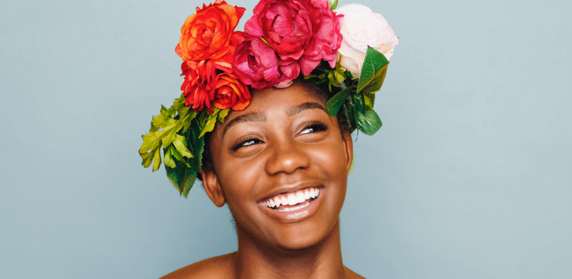 Smiling woman with colourful flowers on head against blue background